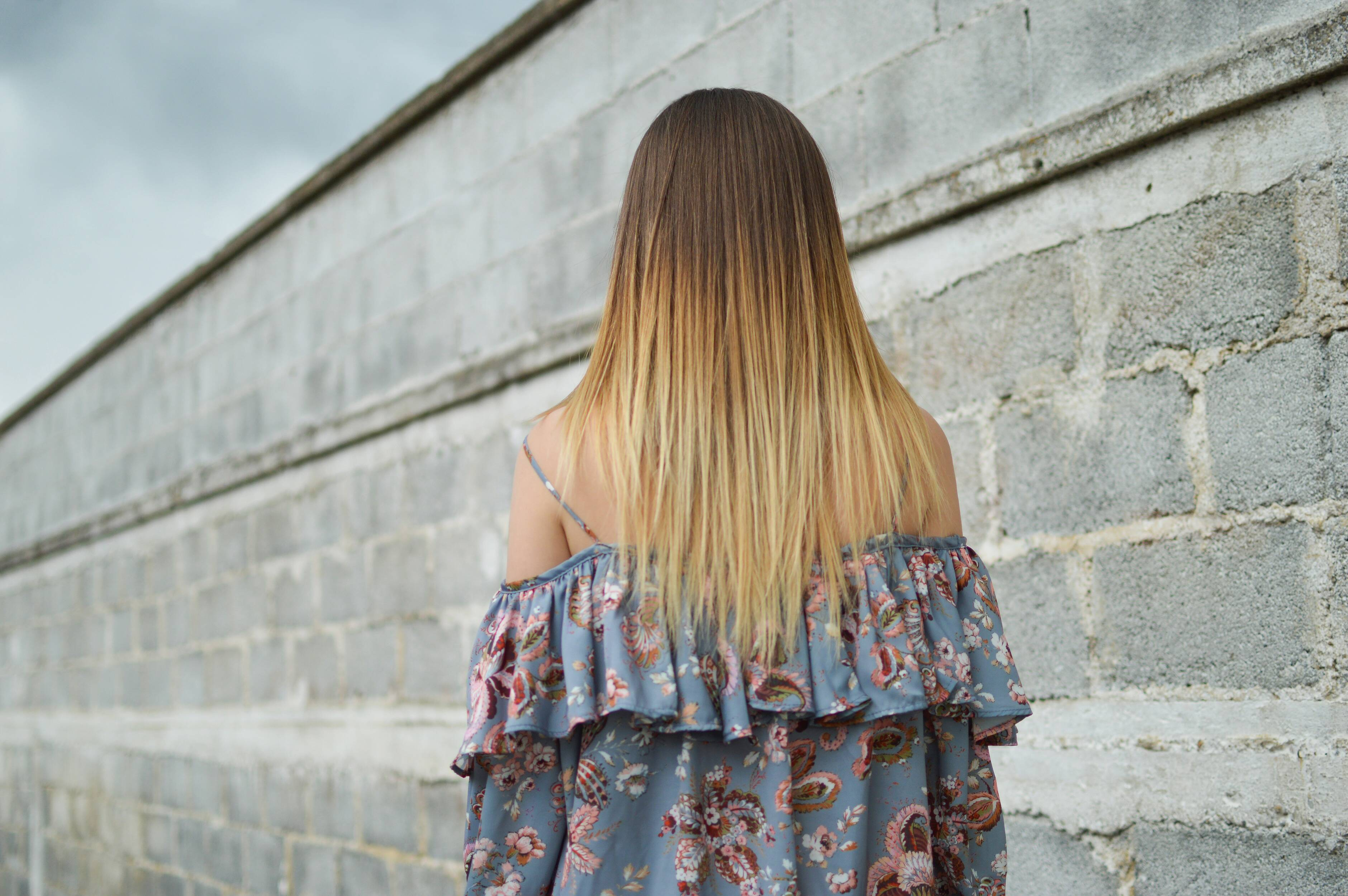 Brunette woman with blonde highlights a blue floral dress beside a stone wall under a gray sky - Ihr Frisör in Kastellaun – Hairpoint